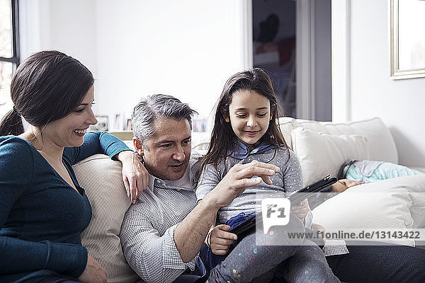 Family using tablet computer while sitting on sofa at home