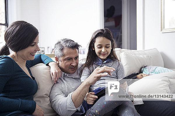 Familie benutzt Tablet-Computer  während sie zu Hause auf dem Sofa sitzt