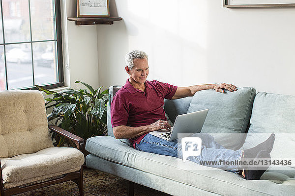 Full length of mature man using laptop computer while resting on sofa in living room at home