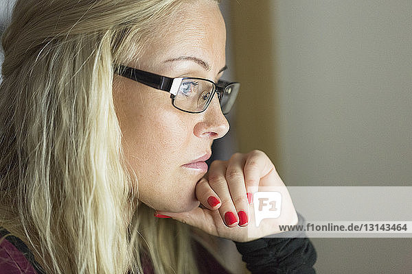 Nahaufnahme einer nachdenklichen Frau mit Hand am Kinn  die zu Hause sitzt