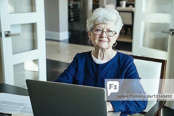 Porträt einer älteren Frau  die zu Hause einen Laptop benutzt