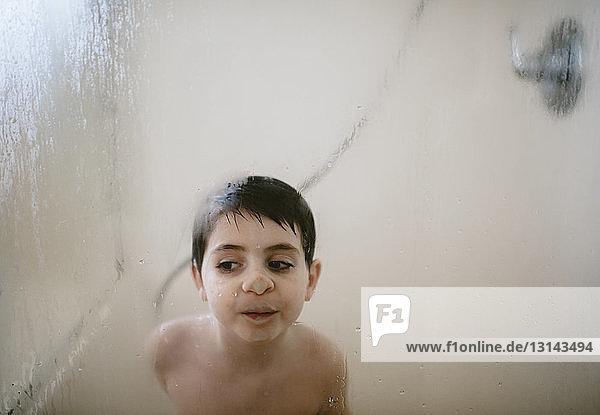 Shirtless boy pressing nose on condensed window in bathroom