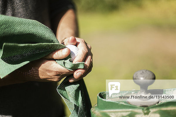 Cropped image of man cleaning ball at golf course