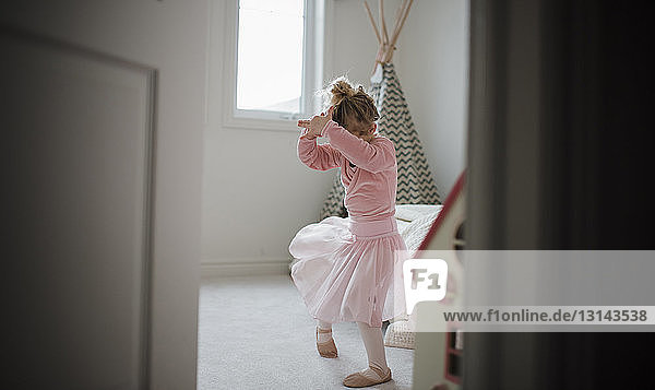 Girl in ballet costume dancing at home seen through doorway