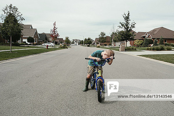 Boy riding bicycle on road against cloudy sky