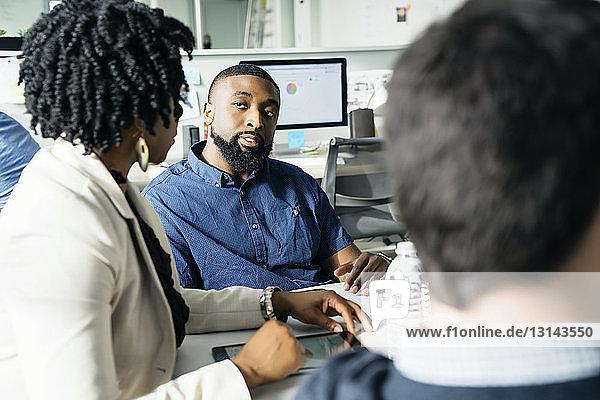 Geschäftsmann betrachtet weibliche Geschäftskollegin während einer Diskussion im Amt