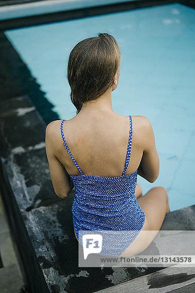 Schrägansicht einer jungen Frau im einteiligen Badeanzug  die am Pool sitzt