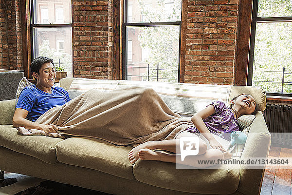 Cheerful father and daughter relaxing on sofa at home