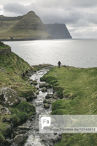 High angle view of hiker standing by sea against cloudy sky
