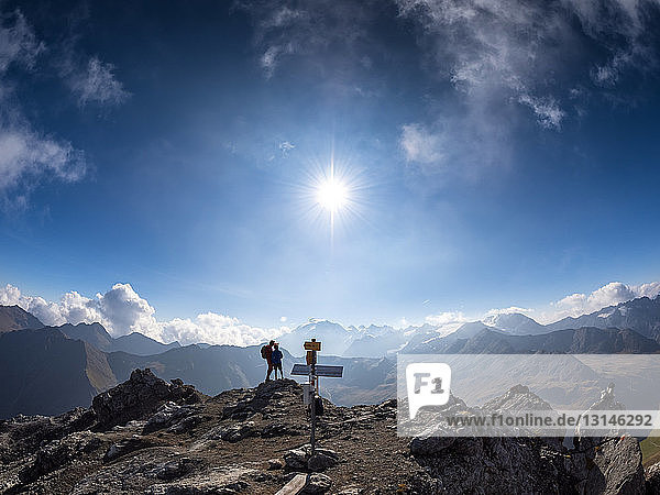 Border region Italy Switzerland  father and son on peak of Piz Umbrail