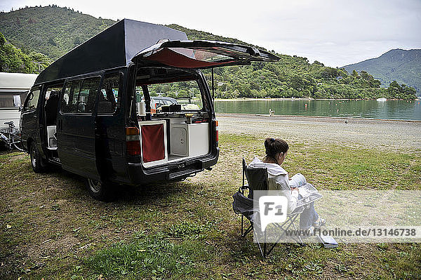 Woman sitting by campervan  New Zealand