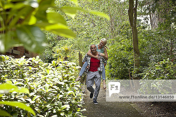 Happy couple having fun giving piggy back in garden