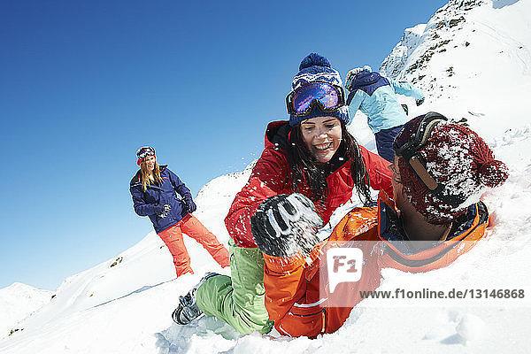 Friends play fighting in snow  Kuhtai  Austria