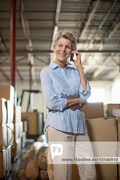 Female warehouse worker on cell phone