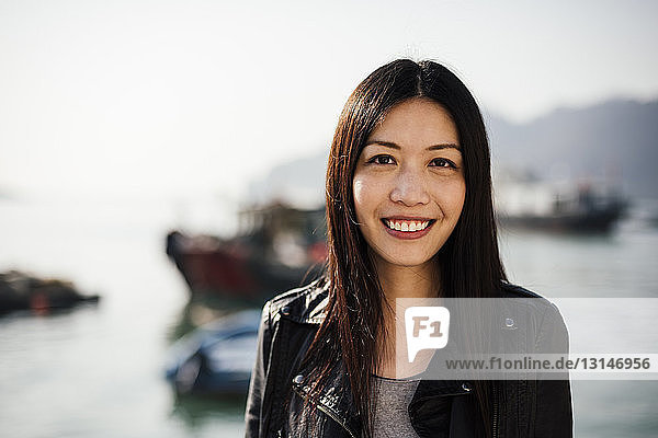 Portrait of young woman in front of boats on water  looking at camera smiling