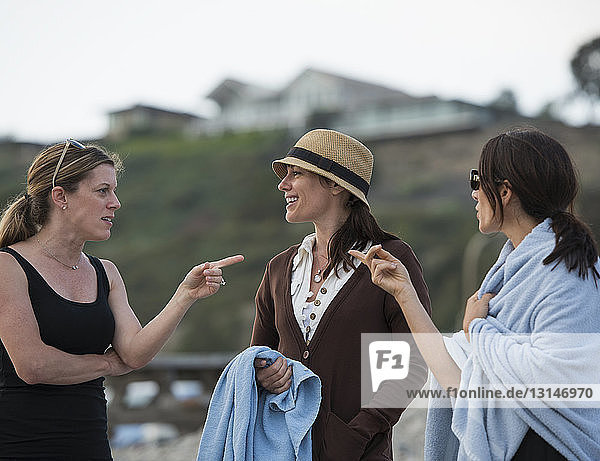 Three adult female friends pointing at each other and chatting on beach