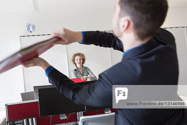 Office worker hitting paper ball with file