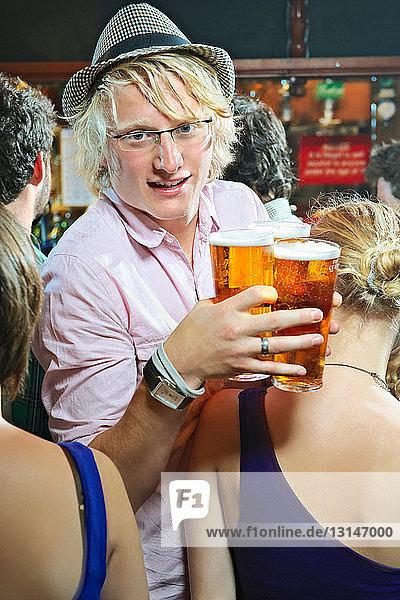 Man holding glasses of beer