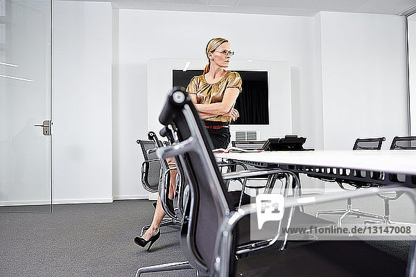 Businesswoman sitting on table in conference room