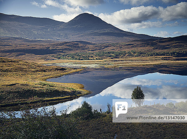 Man photographing reflection of mountain in loch  Highland  Scotland