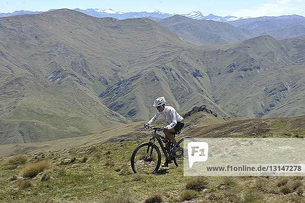 Female mountain biker in mountains  New Zealand