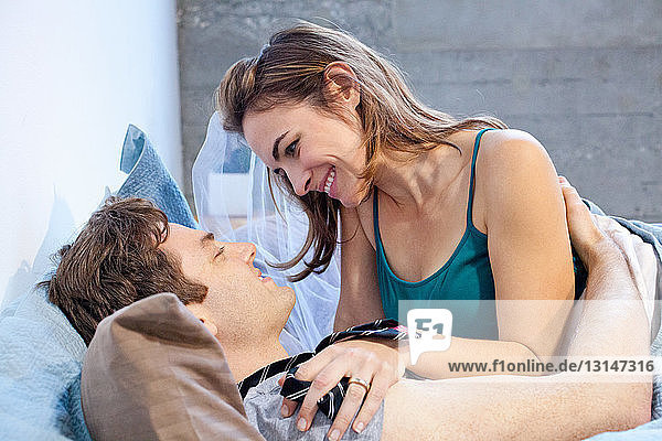 Young newlywed couple relaxing in bed