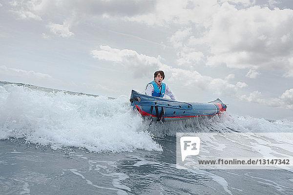 Businessman pushing canoe in ocean Businessman pushing canoe in ocean
