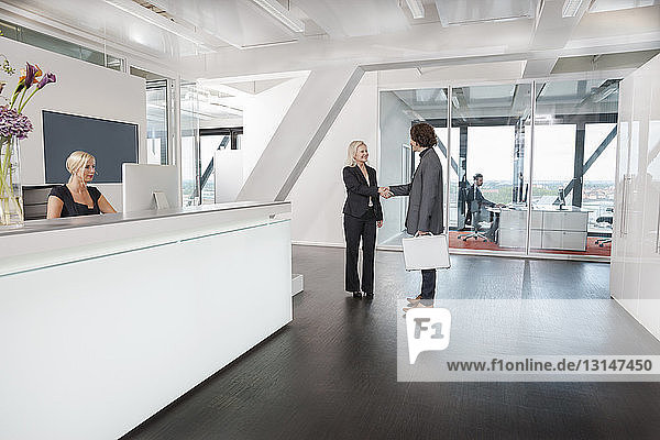 Woman shaking hands with visitor at reception