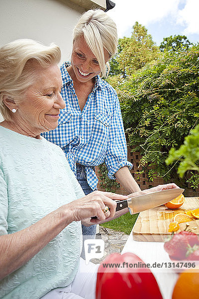 Grandmother and granddaughter chatting while preparing food at garden table