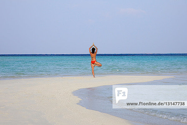 Woman practicing yoga on tropical beach