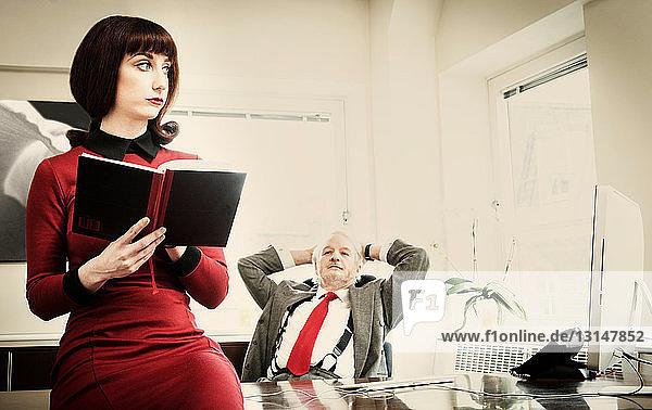 Senior manager at desk watching secretary