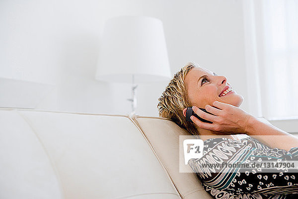 Woman on sofa talking on cell phone