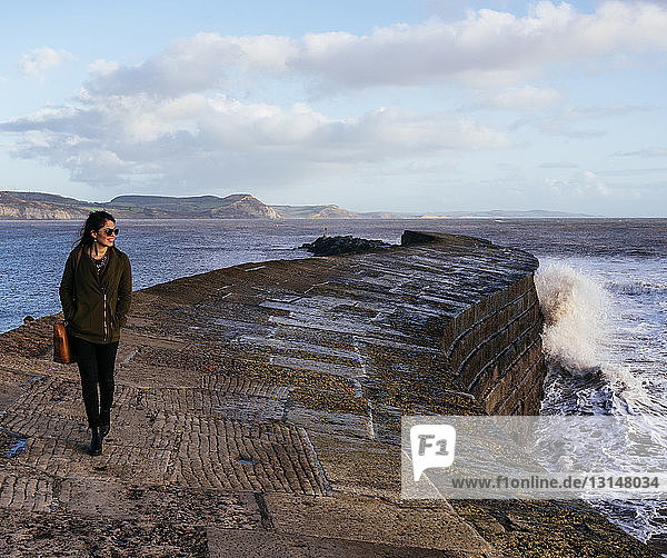 Young woman strolling along 'The Cobb' harbour wall  Lyme Regis  Dorset  England