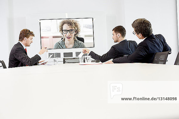 Businessmen sitting around conference table having video conference with woman