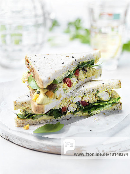Classic coronation chicken salad sandwich with spinach on garden table