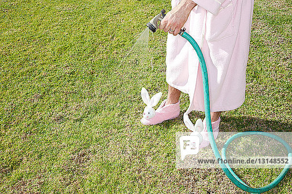 Man in pink robe and bunny slippers watering lawn