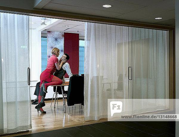 Woman seducing man in board room