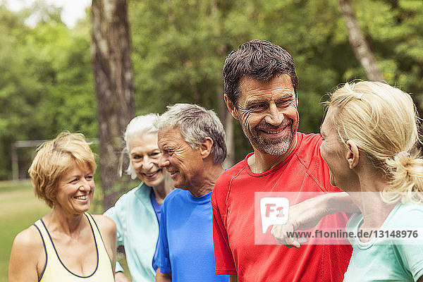 Group of adults outdoors  wearing sports clothing  smiling