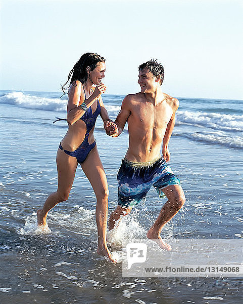 Couple running in waves on beach