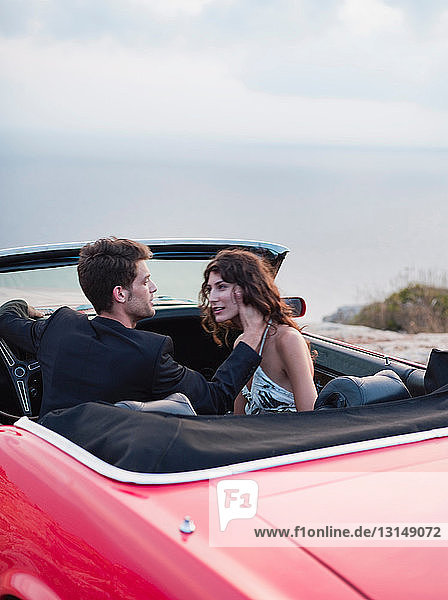 couple sitting in open-topped car