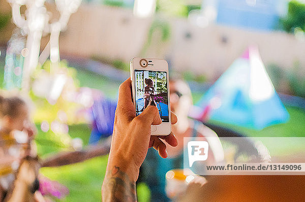 Mid adult man photographing friends on smartphone in garden