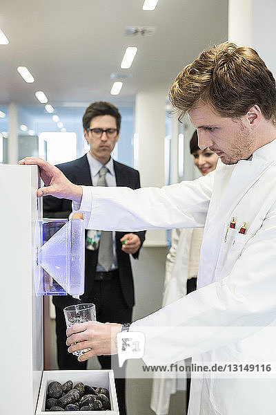 Man wearing lab coat getting drink from water cooler