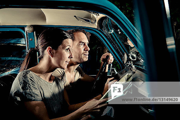 Couple reading map in car at night