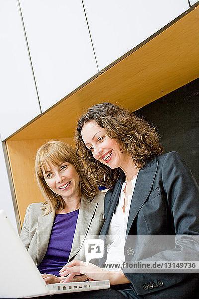 2 businesswomen using laptop