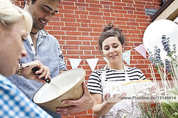 Three friends preparing fruit flan and meringue at garden party