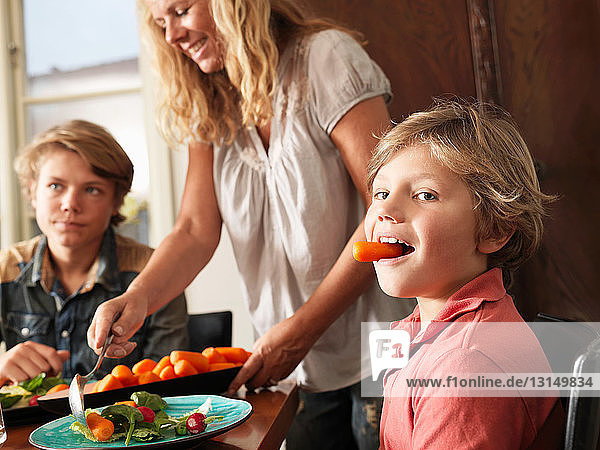 Boy holding carrot in his mouth as mother serves healthy meal