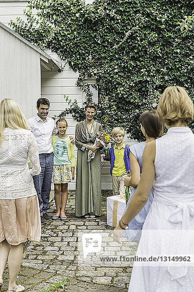Three generation family greeting each other in garden with birthday gifts