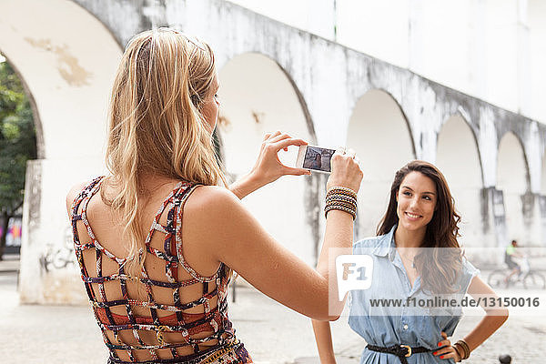 Young woman taking photograph of friend in front of Carioca Aqueduct  Rio de Janeiro  Brazil