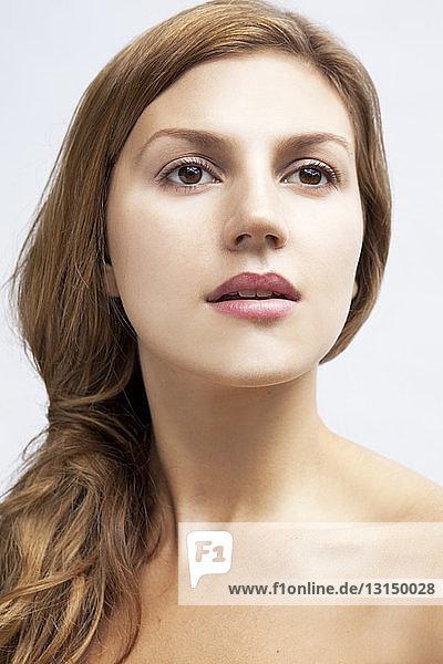 Studio portrait of beautiful young woman gazing
