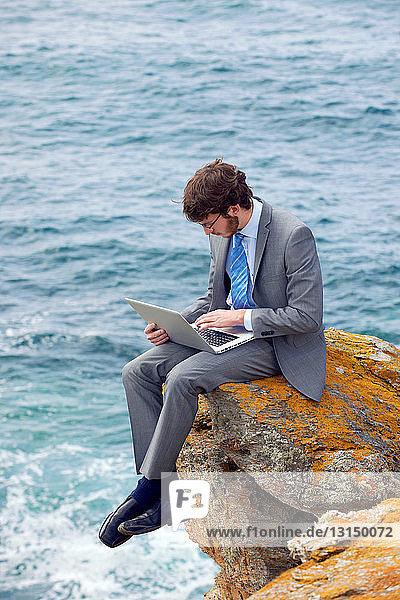 Businessman using laptop on cliff